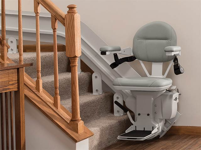 Updated Bruno Elite Curved Stairlifts in warm gray at the bottom of staircase